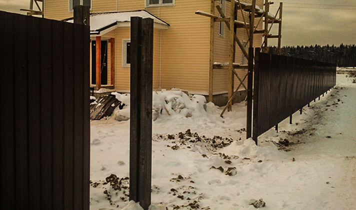 Новый забор рядом с домом зимой