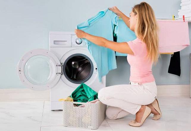 Женщина вытаскивает белье