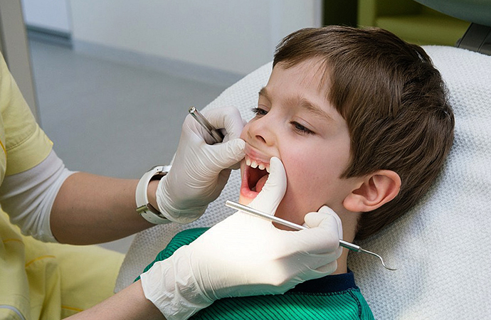 Стоматолог осматривает зубы у ребенка