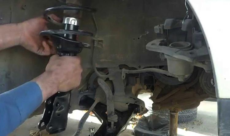 Профессионал ремонтирует амортизатор