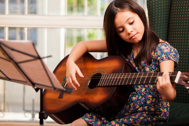 Девочка учится играть на гитаре