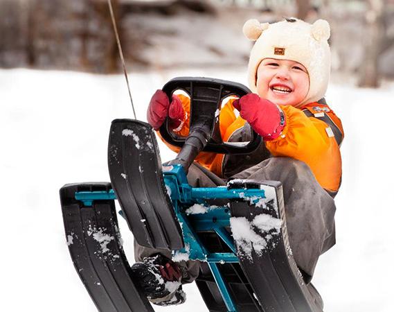 Довольный ребенок на снегокате