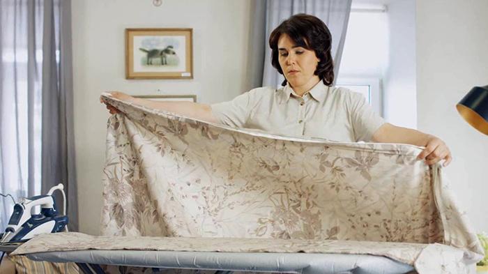 Хозяйка гладит постельное белье
