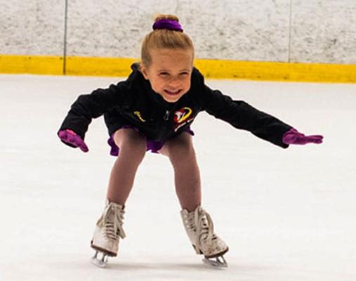Девочка пытается стоять на коньках