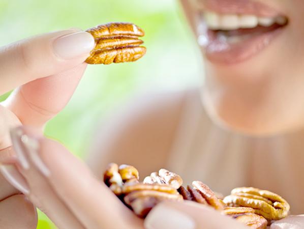 Девушка кушает орехи пекан