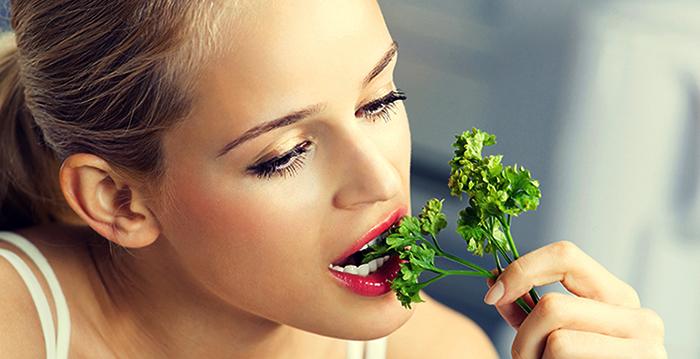 Девушка кушает петрушку