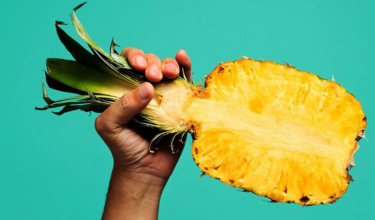 Разрезанный ананас в руках