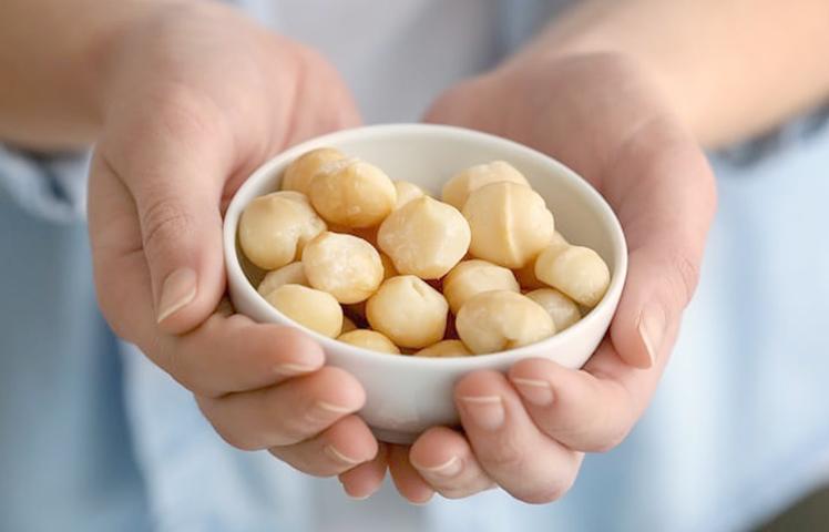Орехи макадамия в руках