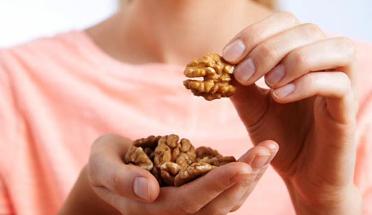 Девушка ест грецкие орехи